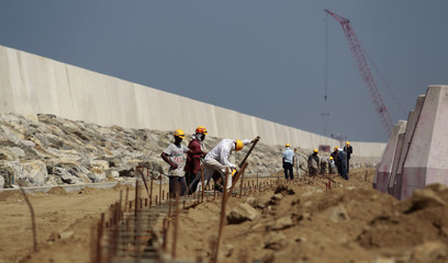 Employees work at the construction site of a Colombo port