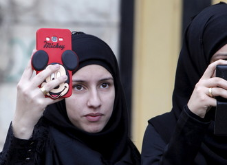 A woman takes pictures with her Mickey Mouse covered mobile phone as she attends the funeral of three Lebanon's Hezbollah fighters who were killed while fighting alongside Syrian army forces in Syria in Nabatieh town