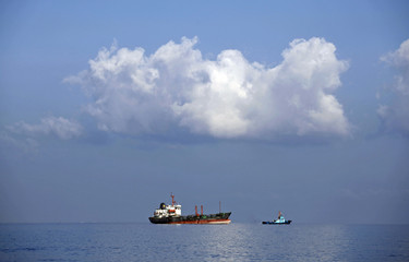 "An old oil tanker named ""Sail Peter"" is tugged out to sea from Havana's port"
