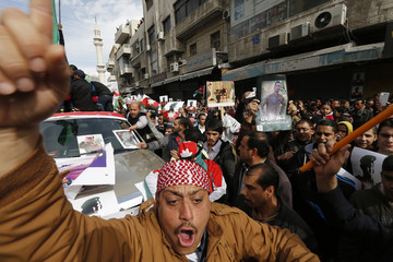 Jordanian protesters hold up pictures of Jordanian King Abdullah and Jordanian pilot Muath al-Kasaesbeh, as they chant slogans during a march after the Friday prayers in downtown Amman