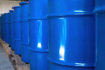 Blue barrels on pallets in a warehouse ready for export