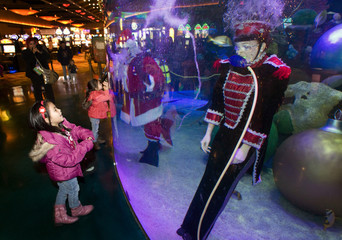 Two girls visit an underwater Santa Claus and his helpers swimming in an aquarium in Las Vegas