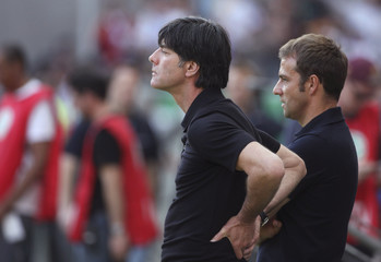 Germany's national coach Loew and assistant coach Flick look on before their friendly soccer match against Bosnia-Herzegovina in Frankfurt