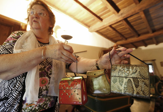 Dardenne shows lithographed tin boxes, dating from the 20th century which were also used as toy handbag for young girls, at her house in Grand-Hallet