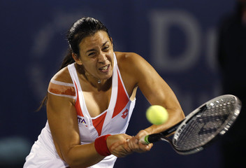 Bartoli of France hits a return to Wozniacki of Denmark Marion during their women's singles quarter-final match at the WTA Dubai Tennis Championships