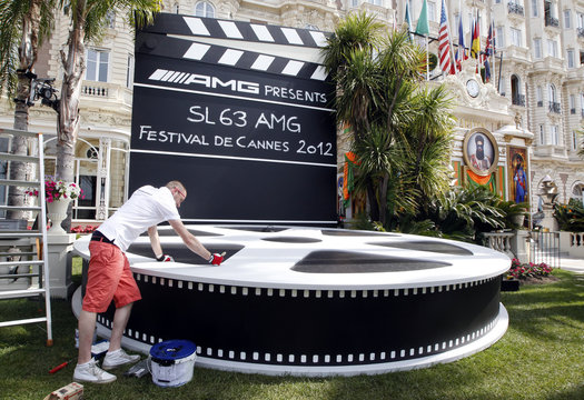A worker paints a giant film reel of the 65th Cannes Film Festival in front of the Carlton Hotel on the eve of the start of the festival in Cannes