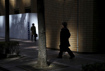 Businessmen walk along commercial buildings in Tokyo