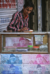 A money changer uses a calculator while sitting at his roadside booth, decorated with photos of Pakistani rupee, in Karachi