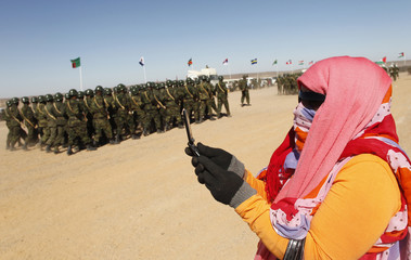 A Sahrawi woman takes a picture with her mobile phone during the 35th anniversary celebrations of their independence movement for Western Sahara from Morocco, in Tifariti