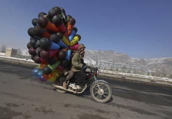 An Afghan man rides on his motorcycle as he sells balloons along a street in Kabul