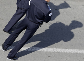 French policemen cast their shadows on the pavement as they stand guard near the Festival Palace during the 69th Cannes Film Festival in Cannes