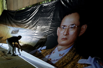 A worker works on a portrait of Thailand's late King Bhumibol Adulyadej at the Bangkok City hall in Bangkok