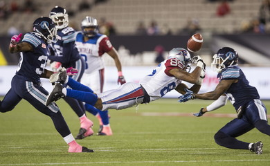 Montreal Alouettes' Cunningham dives for a ball against Toronto Argonauts' Gabriel and Hawkins during their CFL football game in Hamilton, Ontario, Canada