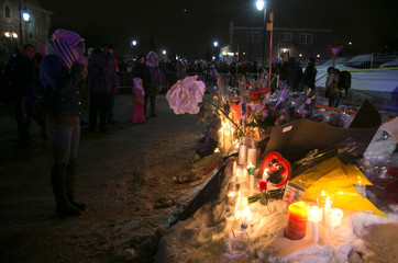 A woman prays at a memorial across the street from the Quebec Islamic Cultural Centre, the site of a shooting in Quebec City, Quebec