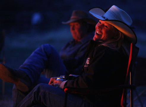 Wrangler Denise Boyd laughs by the campfire during Montana Horses' annual horse drive outside Three Forks