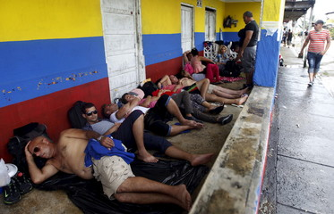Cuban migrants sleep by the doorway of a house as they wait for their flight or boat ticket to continue their journey north, in Puerto Obaldia in the province of Guna Yala, Panama