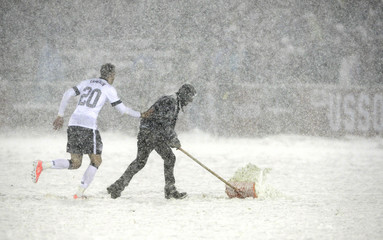 Geoff Cameron of the U.S. helps a field worker shovel snow off the field during the 2014 World Cup qualifying soccer match against Costa Rica in Commerce City
