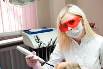 Female dentist examining teeth in dental office