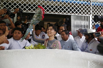 Myanmar pro-democracy leader Aung San Suu Kyi holds up a bouquet of flowers after submitting documents at the Thanlyin election commission office to indicate her decision to run for the Kawhmu constituency in upcoming general election at Thalyin