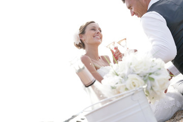 Happy bride and groom celebrating wedding with champagne