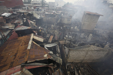Residents search for reusable materials from burnt houses after a fire hit a residential area in Quezon city, metro Manila