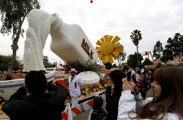 """People take photos of California Milk Advisory Board's """"Legacy of Generations"""" float which was featured in the 128th annual Rose Parade in Pasadena"""