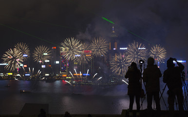 Photographers take pictures during fireworks over Victoria Harbour celebrating the Chinese Lunar New Year in Hong Kong
