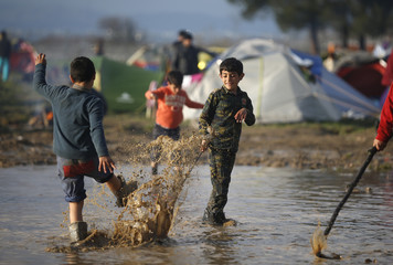 Migrant boys play in the water of the partly flooded makeshift camp on the Greek-Macedonian border near the village of Idomeni