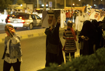 Female supporters carry pictures of Kuwaiti former member of parliament and opposition politician Barrak as they march towards the central prison in Andulos, after a ruling sentenced Barrak to jail for insulting the emir