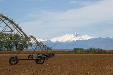 Pivot Irrigation System in a farming field with Longs Peak Mountain in the background