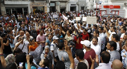 Unemployed graduates chant slogans during a demonstration demanding the right to work in Tunis
