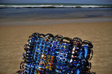 Sunglasses are offered for sale on an empty beach just before Brazil plays Chile in their round of 16 game in Recife