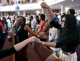 People hold hands during an interfaith vigil at Olivet Baptist church in Chattanooga