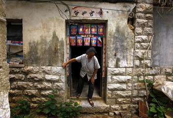 Wang, mother of blind Chinese activist Chen, leaves her son's room at their home in the village of Dongshigu