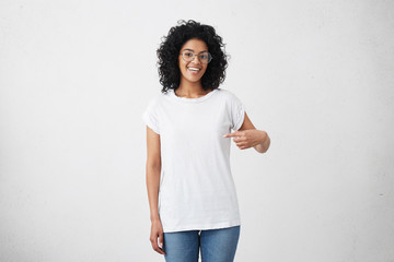 T-shirt design and advertising concept. Style and fashion. Indoor shot of cheerful smiling young African American woman with curly hair pointing index finger at copy space on her blank white top