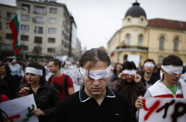 Students with bandages over their eyes take part in a demonstration in Sofia