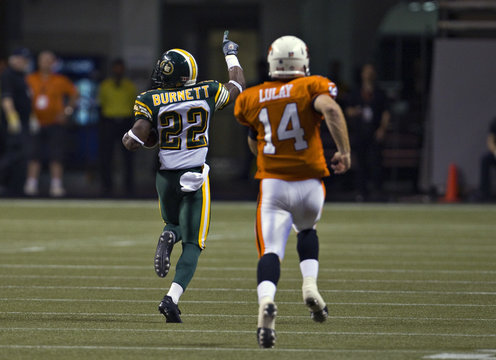 Eskimos cornerback Burnett heads down field chased by BC Lions quarterback Lulay to score a touchdown during CFL football game in Vancouver