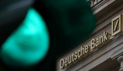 A green traffic light is seen next to the logo of Germany's largest business bank, Deutsche Bank in Frankfurt