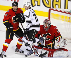 Calgary Flames' Smith reacts as a puck hits Los Angeles Kings' Fraser in front of Flames' MacDonald during their NHL hockey game in Calgary