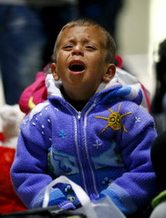 An exhausted young Syrian boy cries after he arrived with his family on a train from Budapest's Keleti station at the railway station of the airport in Frankfurt