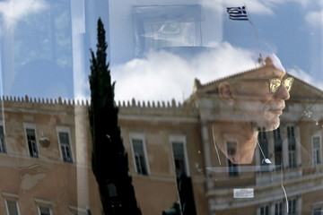 A bus driver looks on as the parliament building is reflected on a bus window in Athens