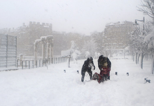 Residents enjoy snow near the ruins of the Roman Temples of Bacchus and Jupiter at the historical ruins of Baalbek in eastern Lebanon