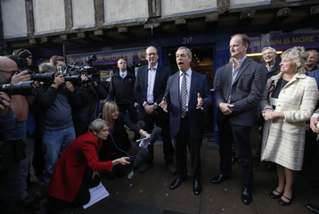 United Kingdom Independence Party leader Nigel Farage speaks alongside former Conservative MP and UKIP candidate Mark Reckless (L) and newly elected UKIP MP Douglas Carswell (R) outside the party campaign office in Rochester southeast England