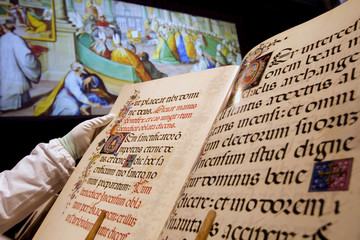 A Vatican librarian, wearing white gloves , turns the pages of a facsimile copy of the Borgianus Latinus in the Vatican