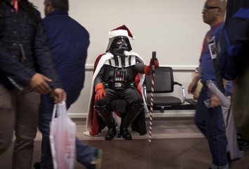 A man dressed up as Santa Vader sits on a bench as people walk past at Comic-Con in New York