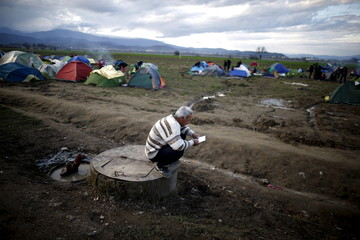 Migrant reads a booklet, informing him about relocation camps inside Greece, as he waits to cross the Greek-Macedonian border at a makeshift camp near the village of Idomeni