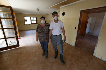 A couple poses for a picture in their flood-affected living room in Fischerdorf, after the waters of the nearby Danube and Isar river subsided in the region's worst floods in a decade