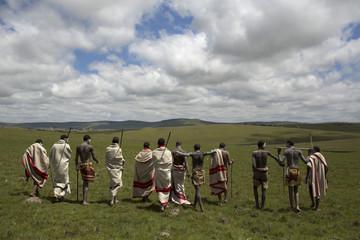 Initiates pose as they walk on a field in Qunu