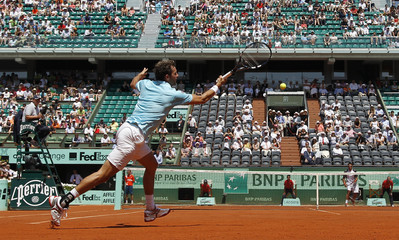 Benneteau of France returns the ball to Tipsarevic of Serbia during the French Open tennis tournament at the Roland Garros stadium in Paris