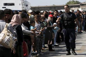 A port police officer gestures to refugees and migrants waiting to board a bus following their arrival onboard the Eleftherios Venizelos passenger ship at the port of Piraeus, near Athens